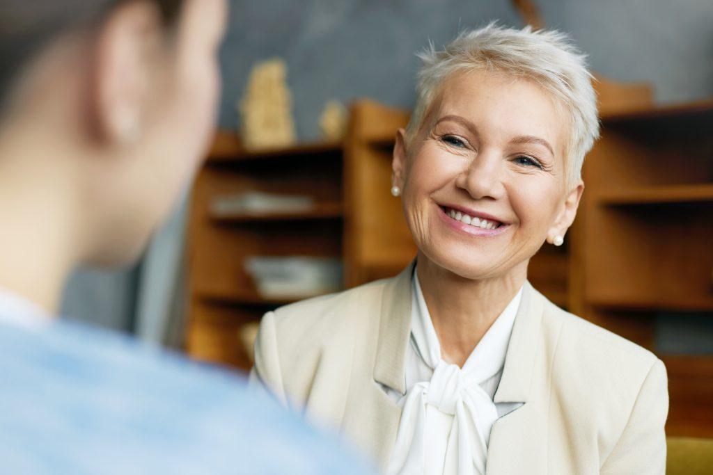 Human resources, recruitment and employment concept. Portrait of beautiful short haired mature woman hr specialist in elegant suit interviewing unrecognizable female job candidate, smiling joyfully